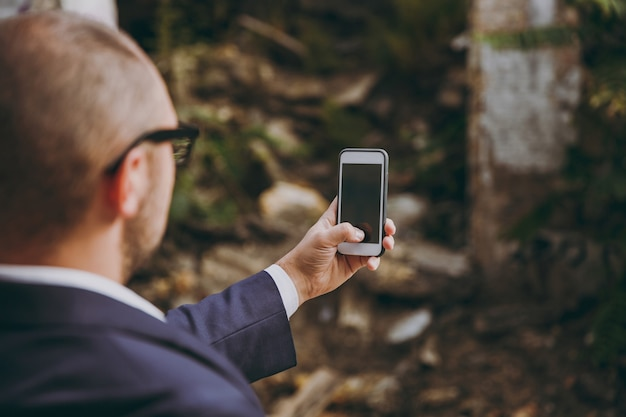 Vue arrière gros plan homme d'affaires recadré en chemise blanche, costume classique, lunettes. homme faisant un selfie au téléphone près des débris de ruines, bâtiment en pierre à l'extérieur. concept de bureau mobile. copiez l'espace pour la publicité.