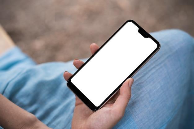 Vue arrière gros plan d'une main de femme à l'aide d'un téléphone intelligent avec écran blanc allongé sur un canapé à la maison.