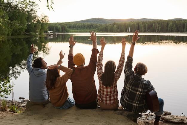 Vue arrière d'un groupe d'amis levant les mains assis au bord du rocher et regardant le lac