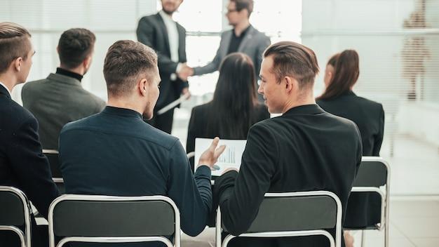 Vue arrière. groupe d'employés assis dans une salle de conférence. affaires et éducation
