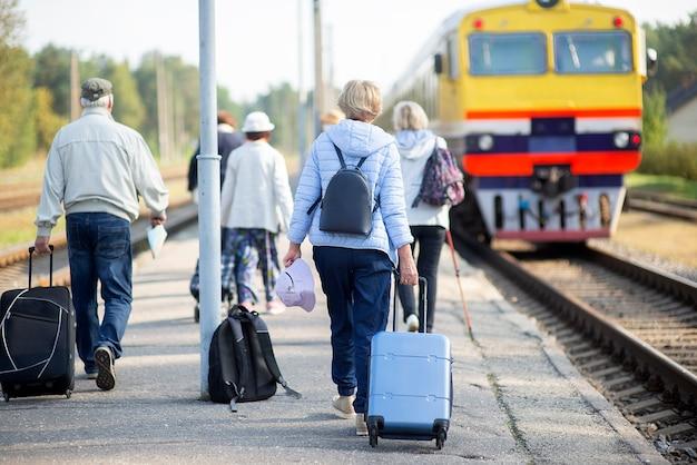 Vue arrière d'un groupe de personnes âgées âgées en attente d'un train pour voyager