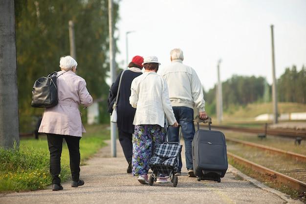 Vue arrière d'un groupe de personnes âgées âgées personnes âgées avec des bagages en attente d'un train pour voyager