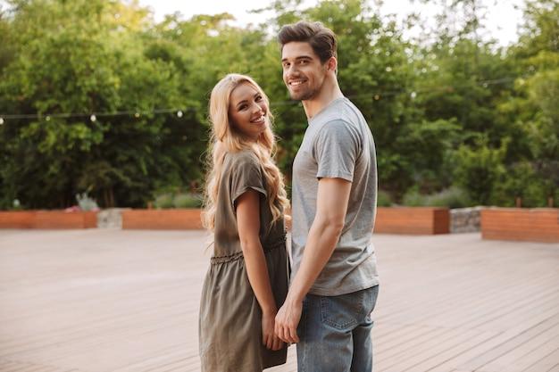 Vue arrière de l'heureux beau jeune couple posant ensemble et regardant la caméra à l'extérieur