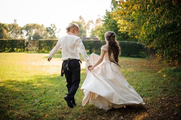 Vue arrière de l'heureux couple marié courir et rire à travers le parc verdoyant le jour d'été