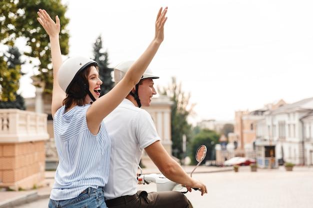 Vue arrière de l'heureux jeune couple en casques de collision à cheval sur un scooter ensemble à l'extérieur