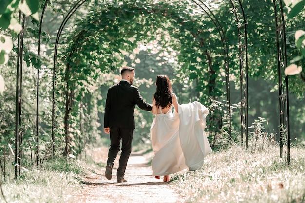 Vue arrière. heureux mariés passant sous l'arche de mariage.