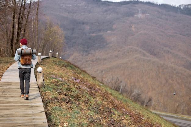 Vue arrière sur hipster traveler male in casual wear marcher seul dans la nature