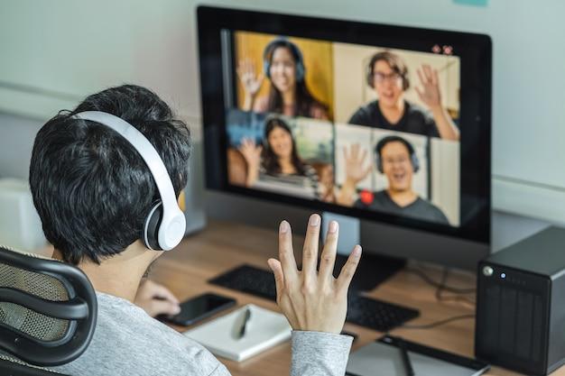 Vue arrière d'un homme d'affaires asiatique dit bonjour avec un collègue de travail d'équipe en vidéoconférence