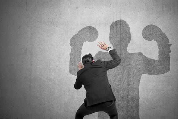 Vue arrière de l'homme d'affaires asiatique peur de l'ombre musculaire sur le mur