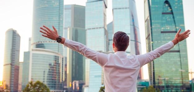 Vue arrière de l'homme d'affaires à la recherche sur l'espace de la copie en se tenant debout contre le gratte-ciel de verre
