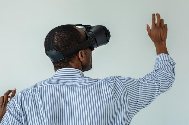 Vue arrière d'un homme afro-américain agréable à l'aide de lunettes vr en se tenant debout contre un mur blanc