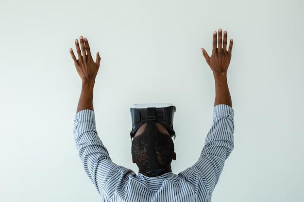 Vue arrière d'un homme afro-américain agréable dans des lunettes vr et tenant la main