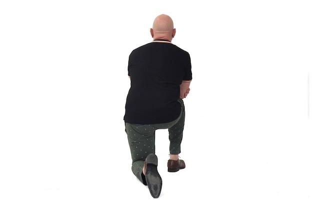 Vue arrière d'un homme appuyé sur un genou au sol sur fond blanc