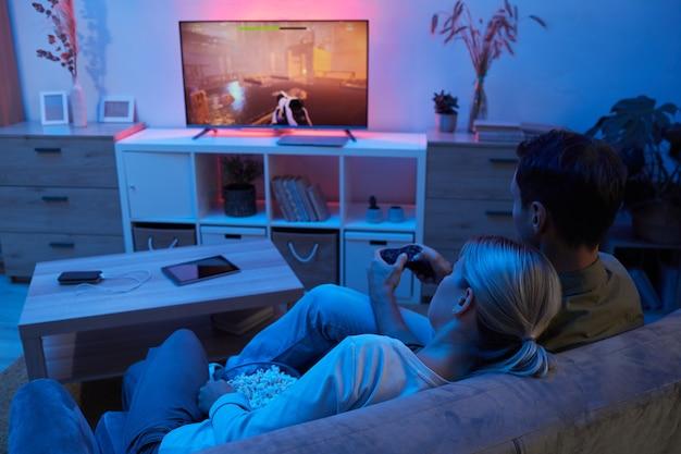 Vue arrière de l'homme assis sur le canapé et jouant au jeu vidéo avec jeune femme mangeant du pop-corn pendant le jeu