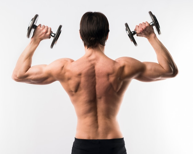 Vue arrière de l'homme athlétique torse nu avec des poids