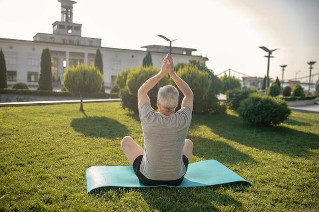 Vue arrière de l'homme aux cheveux gris pratiquant le yoga à l'extérieur, levant les mains au-dessus de la tête