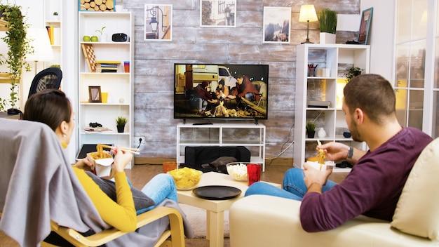 Vue arrière d'un homme barbu avec sa petite amie assis sur des chaises en train de manger des nouilles avec des baguettes devant la télévision. chat qui dort.
