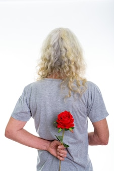 Vue arrière de l'homme barbu senior cachant une rose rouge derrière le dos