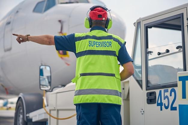 Vue arrière d'un homme dans un casque antibruit debout devant un avion civil