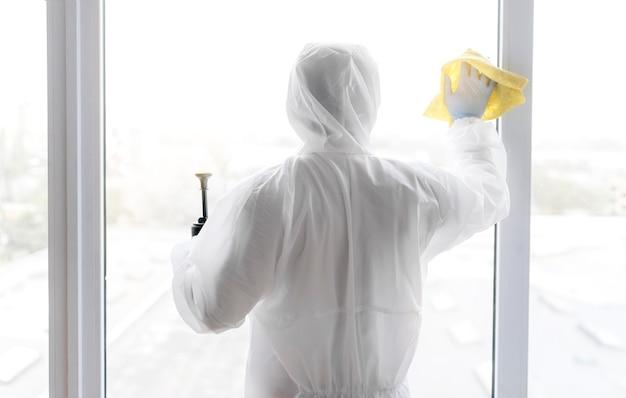 Vue arrière homme désinfectant la fenêtre