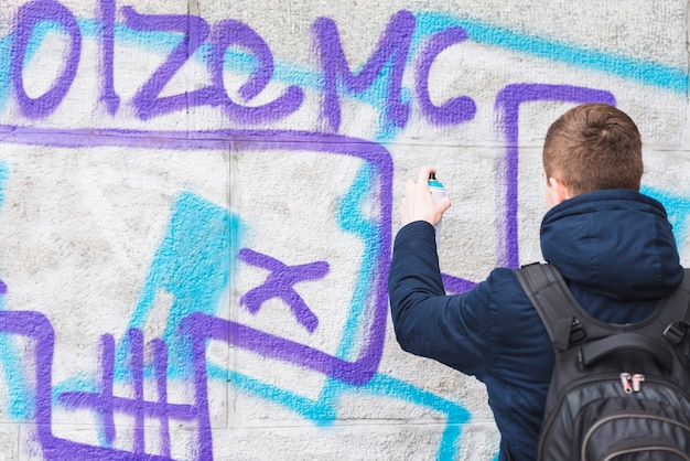 Vue arrière d'un homme dessin graffiti sur le mur