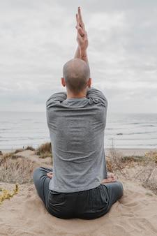 Vue arrière de l'homme à l'extérieur de méditer tout en faisant du yoga
