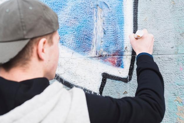 Vue arrière d'un homme faisant des contours de graffiti sur le mur