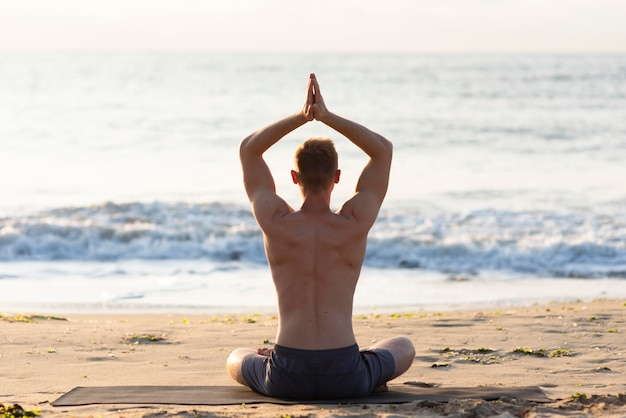 Vue arrière de l'homme faisant du yoga sur la plage à l'extérieur