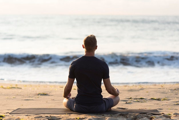 Vue arrière de l'homme faisant du yoga sur le sable