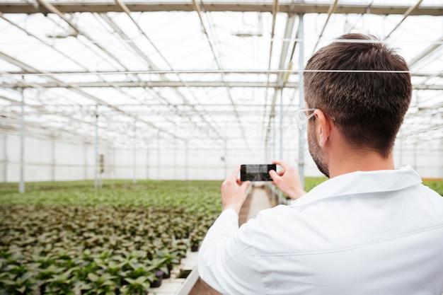 Vue arrière de l'homme faisant une photo de verdure