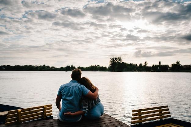 Vue arrière d'un homme et d'une femme romantique assis sur la jetée ou le pont profitant d'un magnifique coucher de soleil. concept de belle famille. jeune couple étreignant et détournant les yeux.