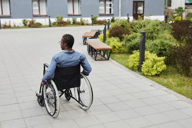 Vue arrière de l'homme handicapé afro-américain avançant en fauteuil roulant tout en marchant dans la rue