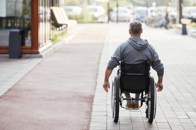 Vue arrière de l'homme mature handicapé équitation en fauteuil roulant le long de la rue