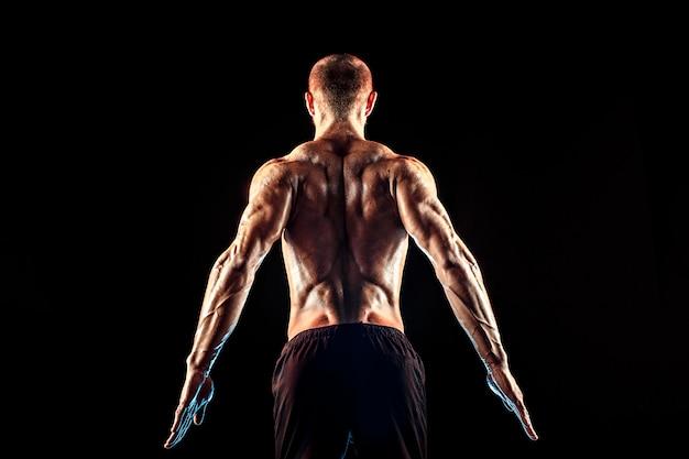 Vue arrière de l'homme méconnaissable, muscles forts posant avec les bras vers le bas. isoler