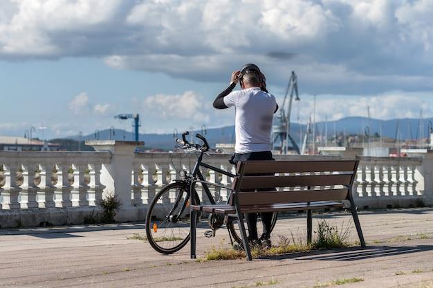 Vue arrière d'un homme mettant son casque avant de faire du vélo le long de la promenade de la ville