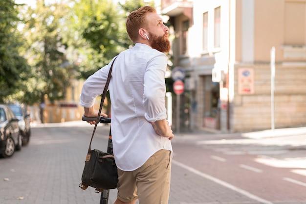 Vue arrière de l'homme moderne sur le scooter à l'extérieur