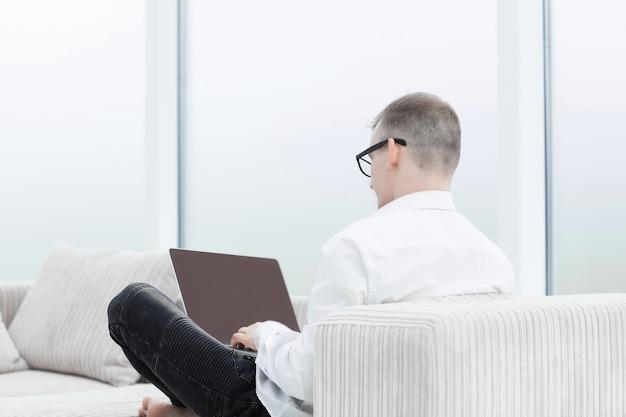 Vue arrière.un homme moderne travaille sur un ordinateur portable dans son salon. photo avec espace copie