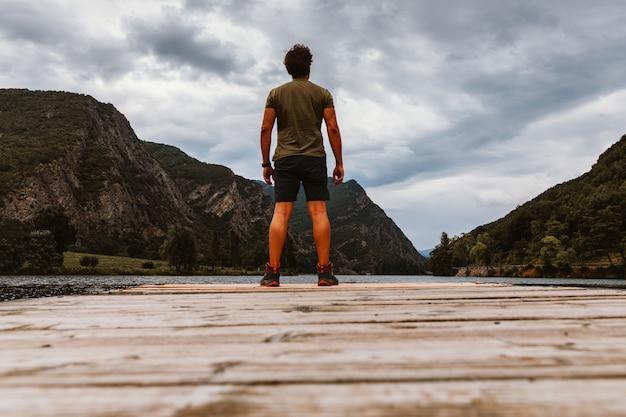 Vue arrière d'un homme sur une passerelle en bois