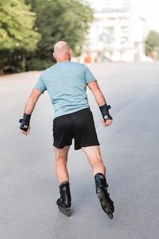 Vue arrière homme portant des patins à roulettes