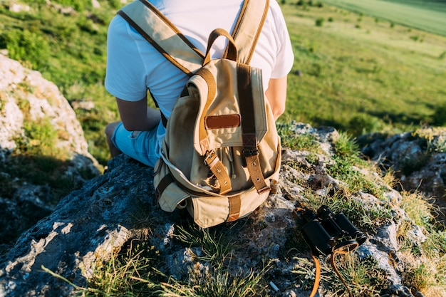 Vue arrière d'un homme avec sac à dos assis sur le rocher