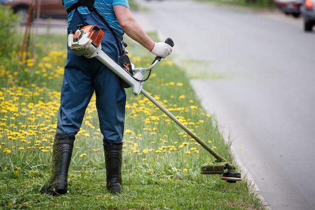 Vue arrière d'un homme en salopette avec une tondeuse à essence tondant l'herbe sur la pelouse