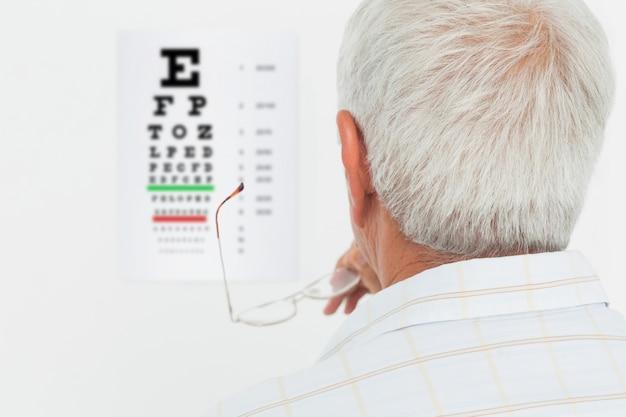 Vue arrière d'un homme senior en regardant la charte de l'oeil