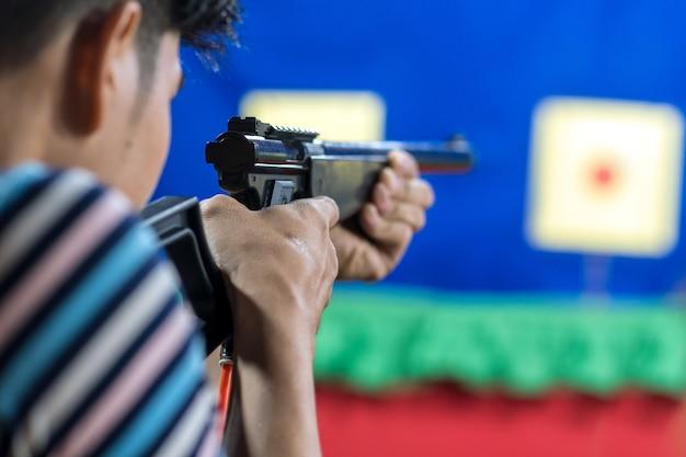Vue arrière de l'homme avec son pistolet sur tir à la cible dans la pratique tir range, sport et soldie