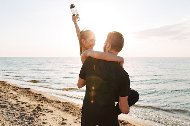 Vue arrière d'un homme de sport tenant sa petite amie heureuse