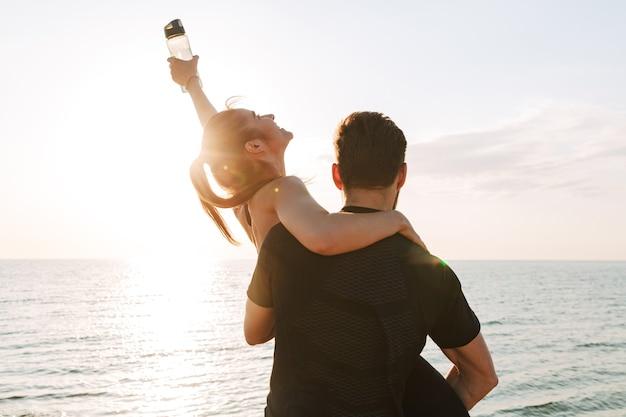 Vue arrière d'un homme de sport tenant sa petite amie