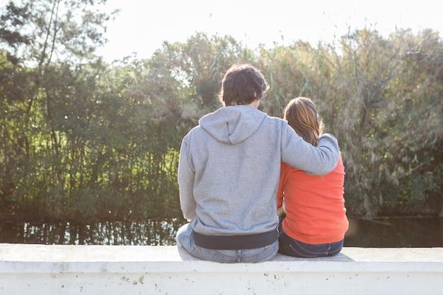 Vue arrière de l'homme sweatshirt porter étreindre sa femme