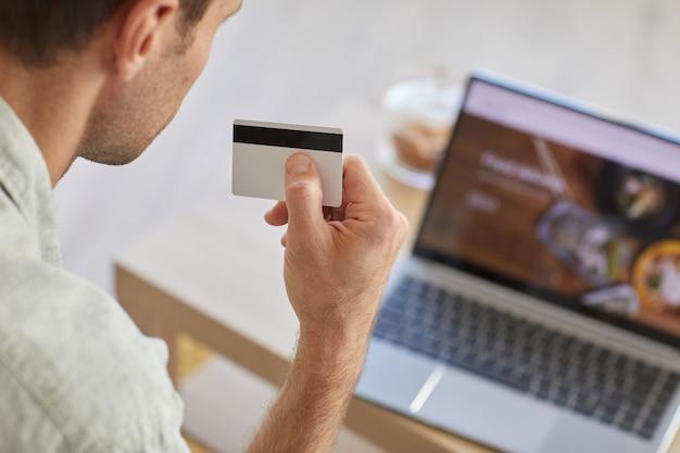 Vue arrière de l'homme tenant une carte de crédit et payer pour la livraison de nourriture en ligne à l'aide d'un ordinateur portable