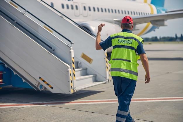Vue arrière d'un homme en uniforme debout devant un camion avec les escaliers d'embarquement des passagers