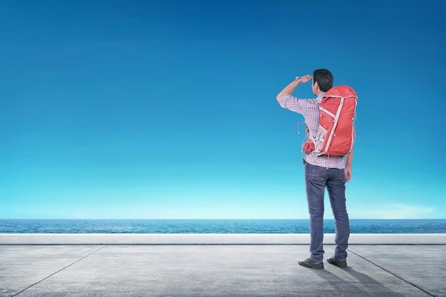 Vue arrière de l'homme voyageur asiatique regardant la vue sur l'océan