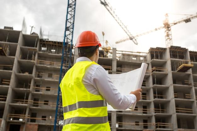Vue arrière sur l'ingénieur sur chantier examine les plans